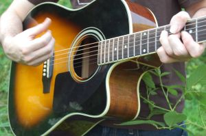 guitarist strumming an acoustic guitar